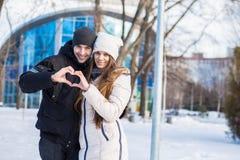 Mooi jong houdend van paar die op een zonnige sneeuwdag lopen royalty-vrije stock fotografie