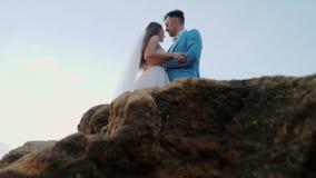 Mooi jong huwelijkspaar die zich op overzeese kust met rotsen bevinden De jonggehuwden brengen samen tijd door: omhels, kus en ge stock videobeelden
