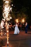 Mooi jong jonggehuwdepaar met brandtoortsen in hun handen en vuurwerk 1 stock fotografie