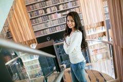 Mooi jong leuk brunette die en in bibliotheek stellen glimlachen stock fotografie