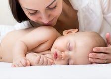Mooi jong mamma die haar bekijken die weinig baby en het glimlachen slapen Kind die in bed thuis liggen Stock Foto
