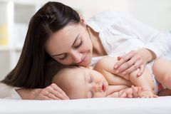 Mooi jong mamma die haar bekijken die weinig baby en het glimlachen slapen Kind die in bed thuis liggen Royalty-vrije Stock Fotografie
