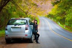 Mooi jong meisje dat aan kant van haar auto rust Stock Foto's