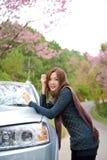 Mooi jong meisje dat aan kant van haar auto rust bij Stock Afbeelding