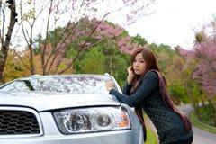 Mooi jong meisje dat aan kant van haar auto rust bij Royalty-vrije Stock Afbeeldingen