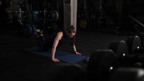 Mooi jong meisje die avondoefeningen doen opdrukoefeningen op de vloer in de geschiktheidsruimte stock video