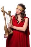 Mooi jong meisje die de harp spelen stock foto
