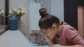 Mooi jong meisje die haar gezicht in bad wassen stock footage