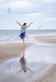 Mooi jong meisje die met zeemeeuwen op het overzees vliegen Royalty-vrije Stock Foto