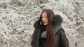 Mooi jong meisje die op de telefoon op de achtergrond van sparren in de sneeuw spreken De dalingen van de sneeuw De winter De ope stock videobeelden
