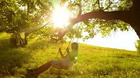 Mooi jong meisje die op schommeling dichtbij een eik slingeren en bij het plaatsen van zon lachen Onbezorgd vermaak van vrije jon stock videobeelden