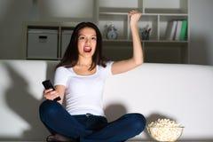 Mooi jong meisje die op TV letten Stock Fotografie