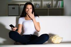 Mooi jong meisje die op TV letten stock foto