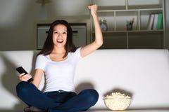 Mooi jong meisje die op TV letten Stock Foto's