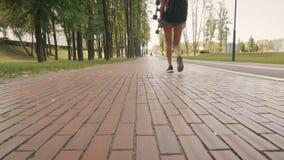 Mooi jong meisje die in park met skateboard lopen stock video