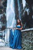 Mooi jong meisje in een blauwe kleding die zich op de achtergrond van een gletsjer en bergen bevinden Stock Foto