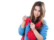 Mooi jong meisje in een blauwe sweater die zich met een rode bal van garen bevinden en een sjaal en Spitz breien Witte achtergron royalty-vrije stock foto