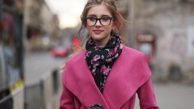 Mooi jong meisje in een elegante blik die onderaan de overvolle stadsstraat lopen, met een kop van koffie en het kijken binnen di stock videobeelden