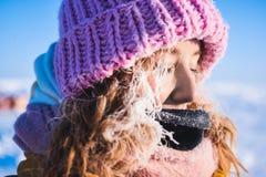 Mooi jong meisje in een geel benedenjasje en roze gebreid GLB met rood haar in een vorst op de achtergrond van het kamp Barneo Stock Fotografie