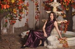 Mooi jong meisje in een kleding dichtbij de fontein Stock Foto's