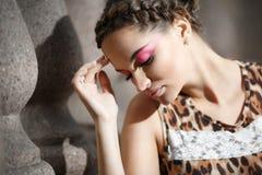 Mooi jong meisje in een kleding van de luipaarddruk stock foto's