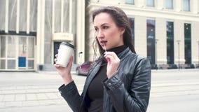 Mooi jong meisje in het zwarte leerjasje knagen aan op zonnebril tegen de achtergrond van een stadsstraat drinkt koffie van stock video