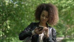 Mooi jong meisje met donker krullend haar die haar celtelefoon met behulp van, openlucht stock video
