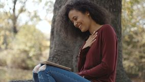 Mooi jong meisje met donker krullend haar die tabletcomputer met behulp van, openlucht stock footage