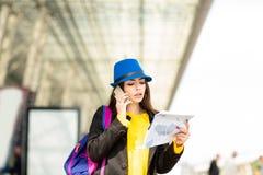 Mooi jong meisje met een rugzak en een blauwe hoed, die op mobiel in de straat dichtbij de luchthaven spreken royalty-vrije stock afbeelding
