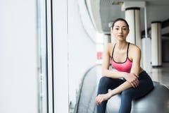 Mooi jong meisje met geschikte bal Geschiktheidsvrouw het uitwerken met pilatesbal, ontspannen en het rusten na training Royalty-vrije Stock Fotografie