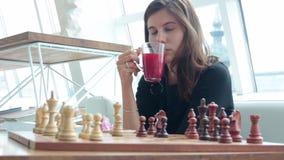 Mooi jong meisje met schaakbord het glimlachen zitting bij lijst in koffie en het drinken thee van glasbeker en bochtig stock footage