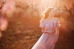 Mooi jong meisje onder de bloeiende roze boom royalty-vrije stock foto's