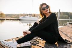 Mooi jong meisje in zonnebril en witte tennisschoenen die op een pijler op een zonnige de zomerdag rusten Stock Fotografie