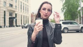 Mooi jong meisje in zwart leerjasje met in hand koffie maakt haar haar recht en draagt zonnebril In de achtergrondpas stock videobeelden