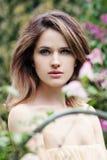 Mooi jong model de lentemeisje in bloemen in bloemenbloesempark Vrouw in een bloeiende tuin stock afbeelding