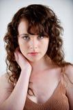 Mooi jong model met het lange krullende haar stellen in een studio Stock Fotografie