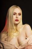 Mooi jong model met lang blondehaar en gouden folie op h Stock Afbeelding