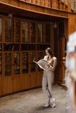 Mooi jong modieus meisje die een boek in de bibliotheek lezen stock foto