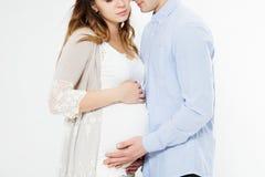 Mooi jong paar die die baby het verenigen en wat betreft buik verwachten op witte achtergrond wordt geïsoleerd royalty-vrije stock foto