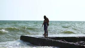 Mooi jong paar die dichtbij het overzees in een onweer lopen De golvenonderbreking over de pijler Een kerel in zwembroek, een mei stock video