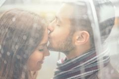 Mooi jong paar die een romantisch teder ogenblik hebben onder de regen - Knappe mens die zijn meisjevoorhoofd kussen stock fotografie