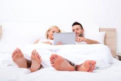 Mooi jong paar die een Tabletpc in Bed met behulp van stock fotografie