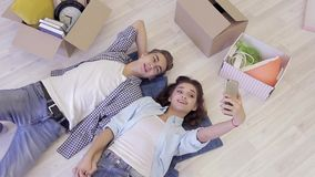 Mooi jong paar die en selfie na zich het bewegen aan een nieuw huis ontspannen maken stock footage