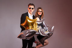 Mooi jong paar die en ster gevormde ballons bevinden zich houden Royalty-vrije Stock Foto's