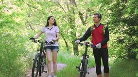 Mooi jong paar die levendig terwijl het lopen met fietsen door park in zomer spreken stock videobeelden