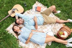 Mooi jong paar die naast elkaar liggen en op een picknickdeken ontspannen, die van hun dag vanaf het stedelijke leven genieten stock foto's
