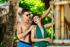 Mooi jong paar die zich naast een bamboehut bevinden op de kust Stock Foto's