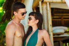 Mooi jong paar die zich naast een bamboehut bevinden op de kust Royalty-vrije Stock Afbeeldingen