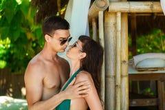 Mooi jong paar die zich naast een bamboehut bevinden op de kust Stock Afbeelding