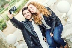 Mooi jong paar die zij mobiele telefoon in het park gebruiken Stock Foto